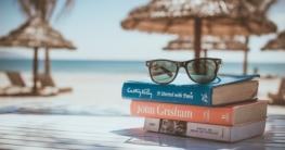 Sonnebrille auf Büchern am Meer